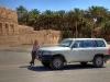 Nikki und Jeep vor großer Lehmburg in einem Palmenhain in Oman