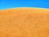 Blauer Himmel über großer goldfarbener Sanddüne, Oman