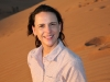 Nikki schaut sich in der Wüste im Oman von der Anhöhe einer Sanddüne den Sonnenuntergang an