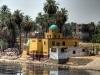 Bunt bemalte ägyptische Häuser am Ufer des Nils. Dattelpalmen stehen dahinter. Foto: www.nikkiundmichi.de