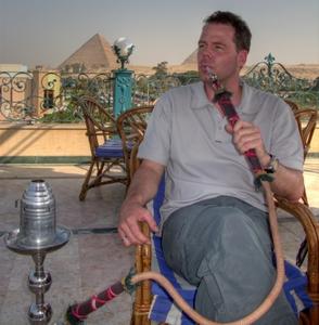 Michi schmaucht eine Shisha (Wasserpfeife) auf der Dachterrase. Dahinter die Pyramiden von Giza. www.nikkiundmichi.de