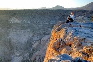 Fernreisen: Nikki sitzt im Hadschar-Gebirge (Oman) auf einer Klippe, genießt den traumhaften Sonnenuntergang. Foto: Michael Dunker