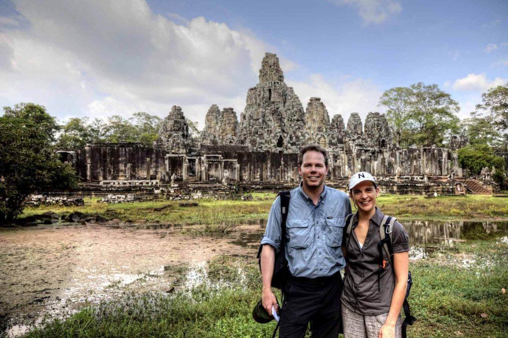 Nicole Bralo-Dunker und Michael Dunker stehen vor dem Bayon Tempel in Angkor Thom, bei Siem Reap.