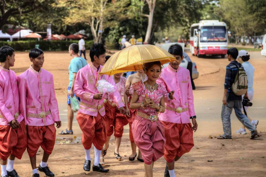 Hochzeit in Angkor Wat - die Braut schreitet grazil voran, die bunte Hochzeitsgesellschaft marschiert hinterher.